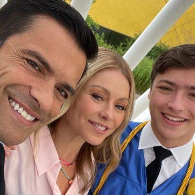 Mark Consuelos, Kelly Ripa, and Joaquin Antonio Consuelos smiling together at a graduation ceremony.