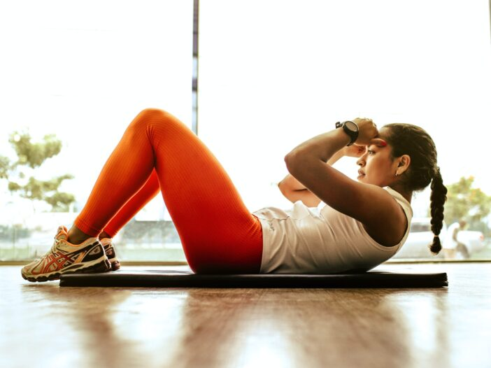 Woman exercising while laying down on a yoga mat.