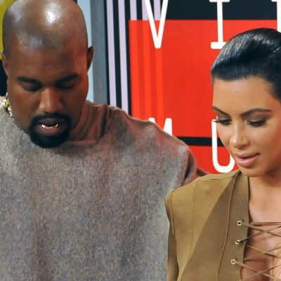 Kanye West wears a gray sweat suit and stands with Kim Kardashian, in an olive dress, at the VMAs