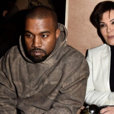 Kanye West, in a camo hoodie, sits with Kris Jenner, in a black top and white blazer