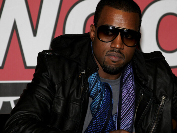 Kanye West in a suit and sunglasses, looking serious