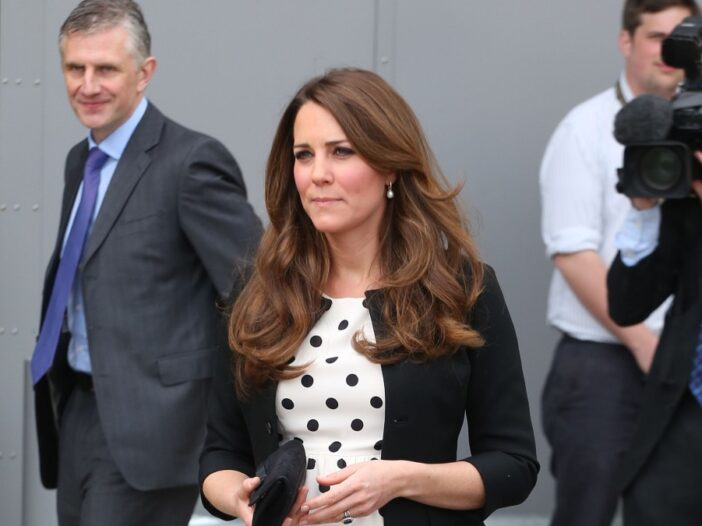 Kate Middleton wears a black sweater over a white dress