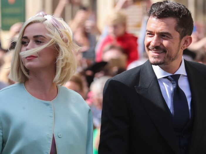 Katy Perry wears a pale blue jacket as she walks with Orlando Bloom, in a dark suit