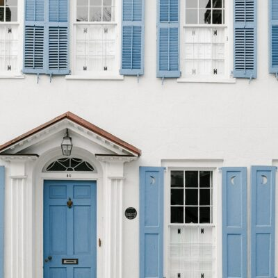 Image of two story home with blue shutters and blue door in Charleston, South Carolina.