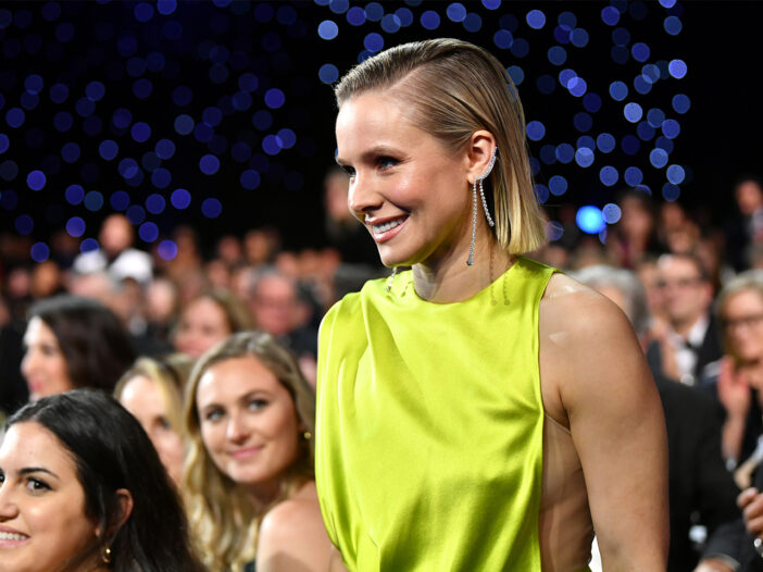 Kristen Bell, smiling in a yellow dress at an awards show.