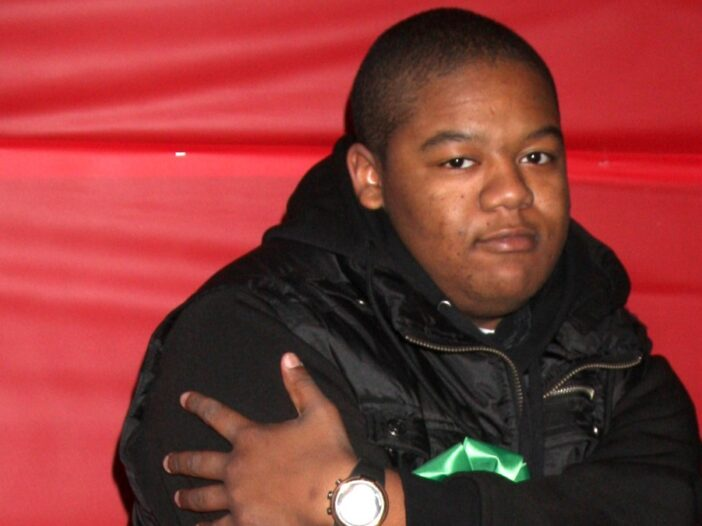 Kyle Massey wears a black jacket and crosses his arms in front of a red backdrop