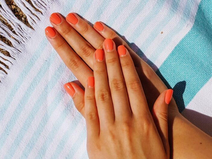 Image of orange painted nail on top of a beach blanket.