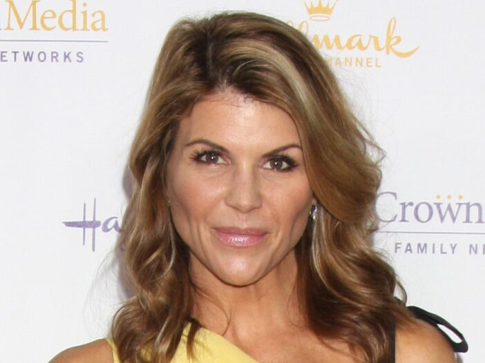 Lori Loughlin wears a yellow dress against a white background on the red carpet
