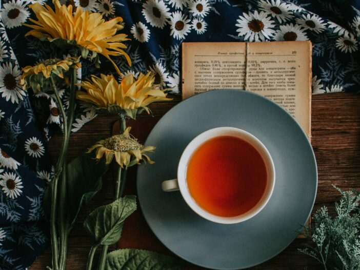 Image of a cup of tea on top of a book and next to some flowers.