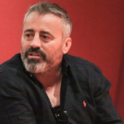 Matt LeBlanc wears a black shirt while sitting on a stage with a red background