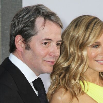 Matthew Broderick wears a black suit as he stands with Sarah Jessica Parker, in a yellow gown