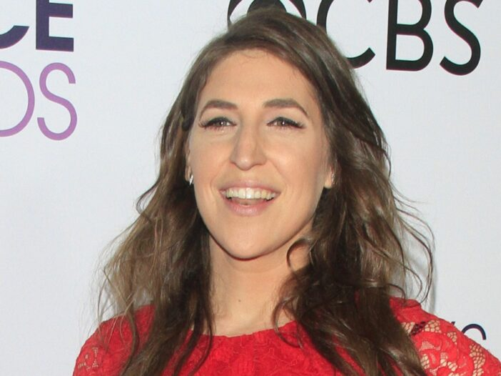 Mayim Bialik wears a red dress against a white background on the red carpet
