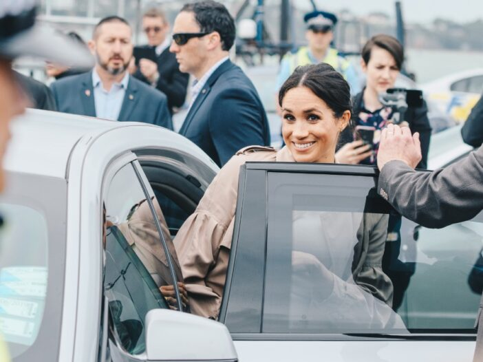Meghan Markle wears a tan coat and smiles as she enters a car