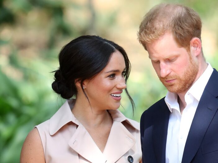 Meghan Markle, in a beige dress, smiles at Prince Harry, in a dark suit, while outside