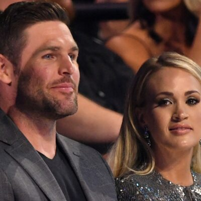 Mike Fisher, in a gray suit, sits with Carrie Underwood, in a silver dress