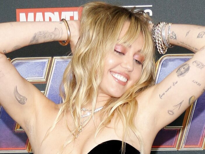 Miley Cyrus strikes a seductive pose while wearing a black dress on the red carpet