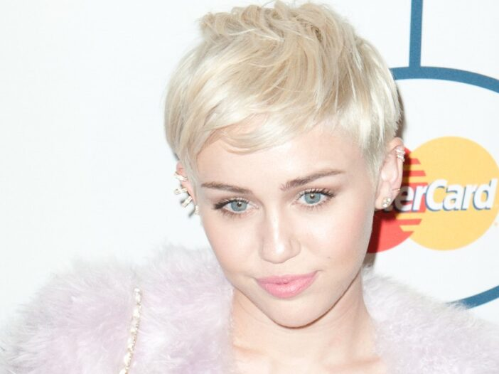 Miley Cyrus wears a feathery pink coat over a short white dress on the red carpet