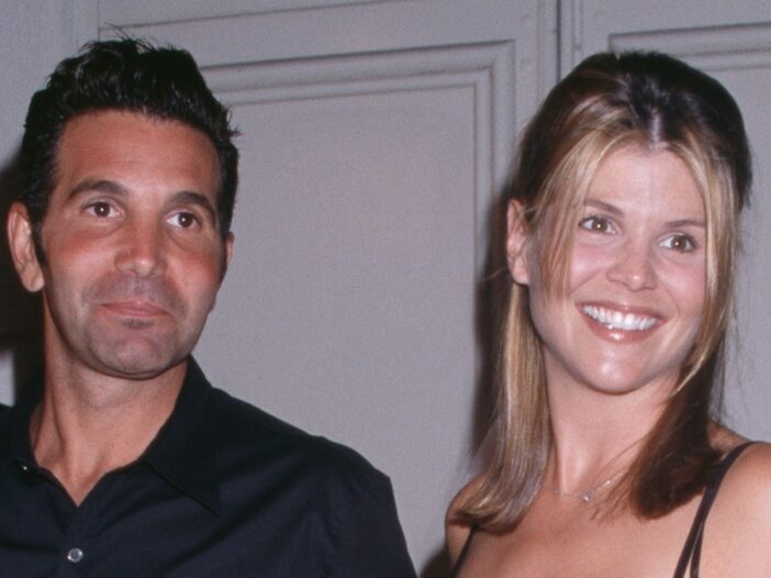 Mossimo Giannulli and Lori Loughlin, both dressed in black, pose for photos