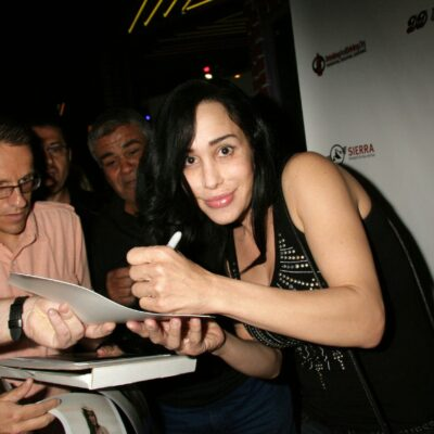 Octomom in a black shirt signing autographs.