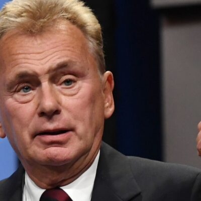 Pat Sajak stands onstage behind a podium wearing a dark suit as he gives a speech