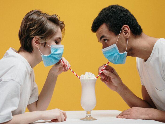 Man and woman sharing a milkshake while wearing masks.
