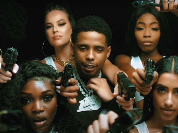 In a music video, Pooh Shiesty (center) stands among five women holding guns