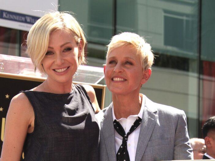 Portia de Rossi wears a black dress and stands with wife Ellen DeGeneres, in a gray suit