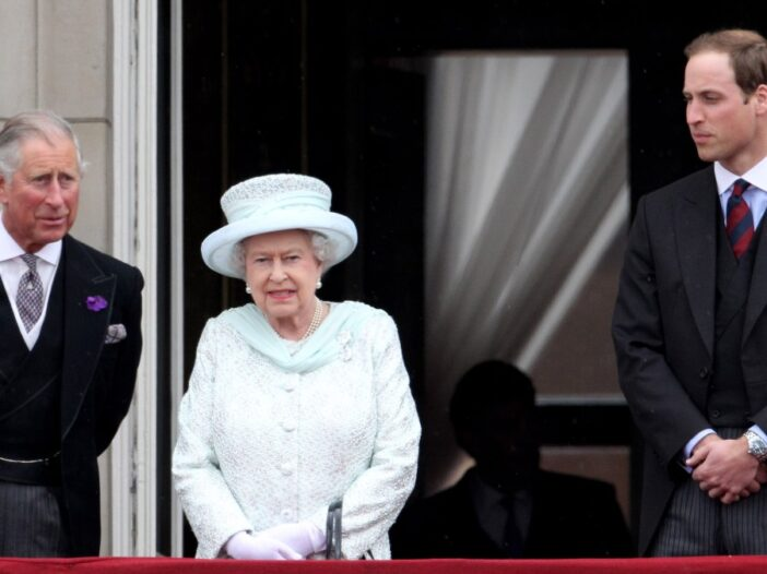 Prince Charles, Queen Elizabeth, and Prince William stand together on a balcony