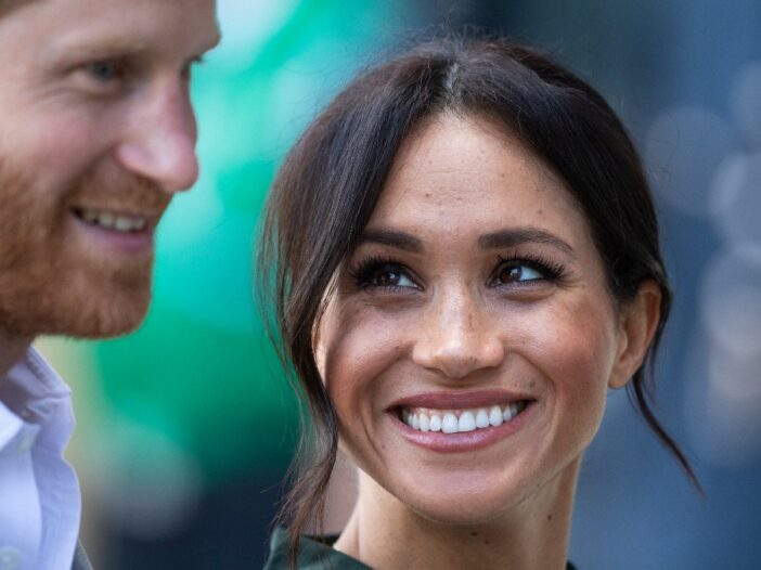 Prince Harry and Meghan Markle smile during a royal event