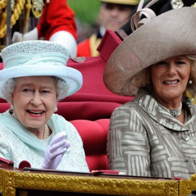 Queen Elizabeth and Camilla Parker Bowles share a carriage and wave to supporters