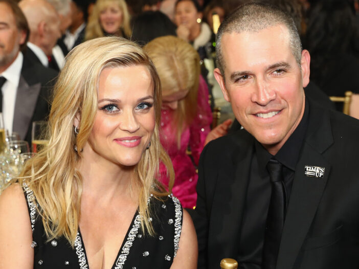 Reese Witherspoon on the left sitting with her husband, Jim Toth.