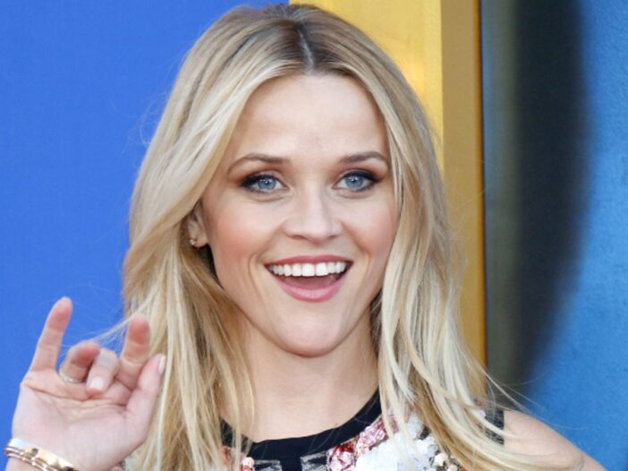 Reese Witherspoon waves and smiles at photographers on the red carpet
