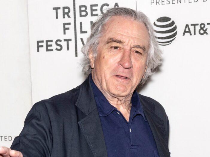 Robert De Niro wears a dark suit jacket against a white background