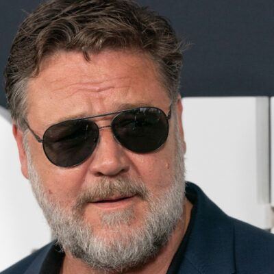 Russell Crowe wears a dark suit and sunglasses on the red carpet