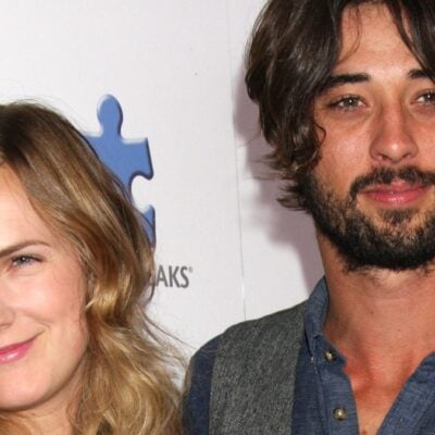 Anna Axster stands with Ryan Bingham on the red carpet