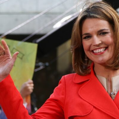 Savannah Guthrie wears a red jacket and waves to an audience from a stage
