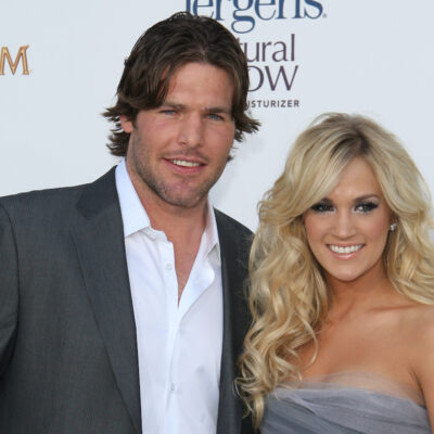 Mike Fisher and Carrie Underwood smiling in grey outfits