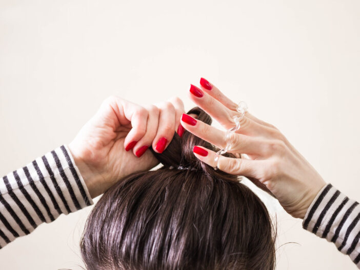 Image of woman doing her hair in a bun.