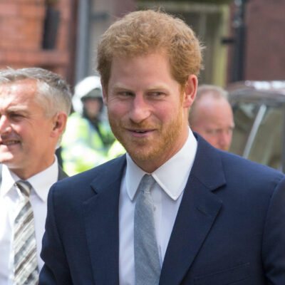 Prince Harry smiling in a navy suit