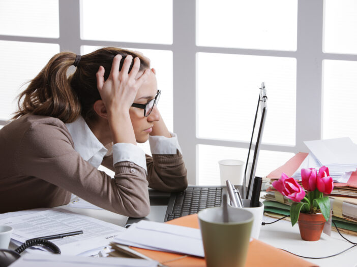 Image of a woman stressed out at work.