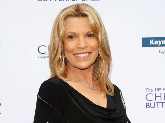 Vanna White smiling in a black blouse