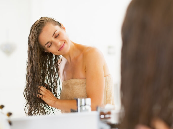 Image of a woman touch washed hair in the mirror.