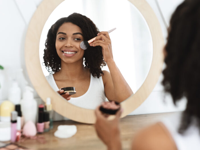 Image of woman applying blush in the mirror.