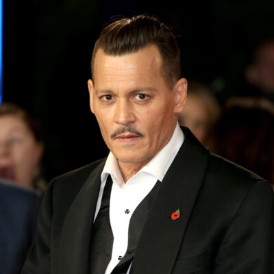 Johnny Depp in a black tux with undone bowtie and slicked back hair at a film premiere.