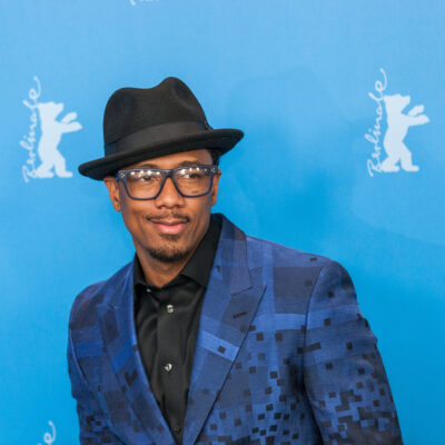 Nick Cannon in a patterned navy suit and black fedora on the red carpet.