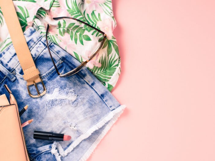 Image of shorts and a Hawaiian style shirt against a pink background.
