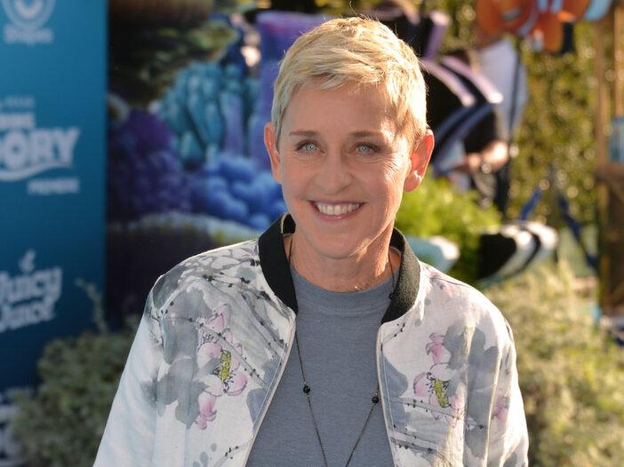 Ellen DeGeneres smiling in a white jacket