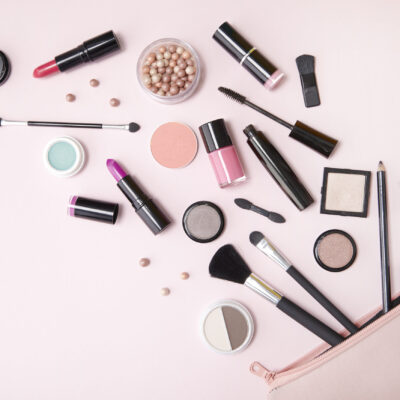 Stock photo of a makeup bag with cosmetics spilling out.