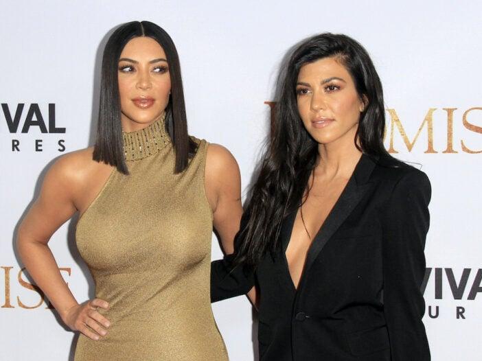 Kim Kardashian in a gold dress staring at Kourtney Kardashian