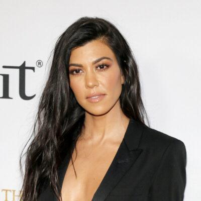 Kourtney Kardashian wearing a low cut black suit jacket on the red carpet.